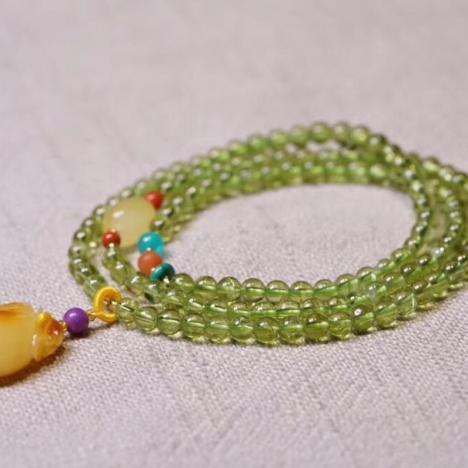 天然橄榄石绕三圏手链,和平之石搭,配蜜蜡钱袋图片